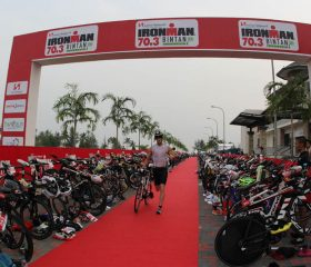 IMB15_Transition_Athlete-running-with-Bike